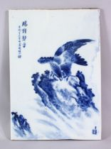 A CHINESE BLUE & WHITE PORCELAIN HAWK TILE / PANEL, depicting a hawk landed upon rocky outcrops