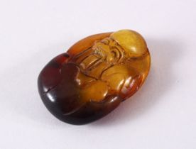 A CHINESE CARVED AMBER FIGURE OF SHOU LAO - carved in deep relief to depict shou lao holding a