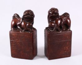 A PAIR OF UNUSUAL TERRACOTTA / POTTERY LION DOG SEAL / DESK WEIGHTS, each dog modeled with their paw