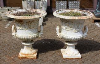 A GOOD PAIR OF VICTORIAN WHITE PAINTED CAST IRON CAMPAGA VASES with mask handles on square bases.