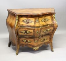 A GOOD SERPENTINE FRONTED BOMBE COMMODE, with cross banded top three long drawers with ormolu mounts