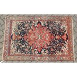 A GOOD MALAYER RUG, red ground with stylised floral decoration within, a pale blue border. 6ft 10ins