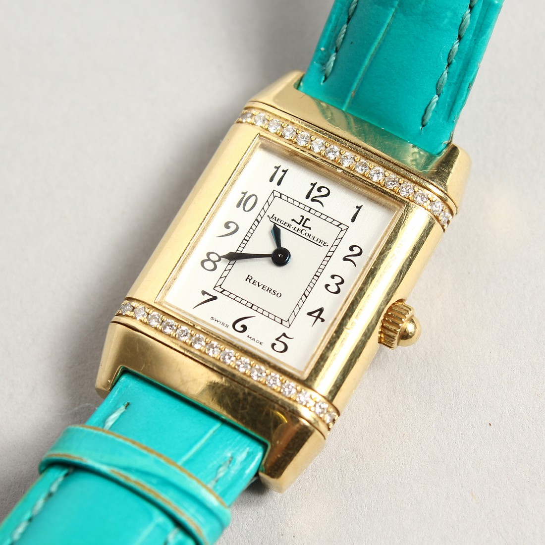 A VERY GOOD 18CT. GOLD AND DIAMOND JAGEUR LE COUTRE REVERSE WRISTWATCH, with a leather strap.