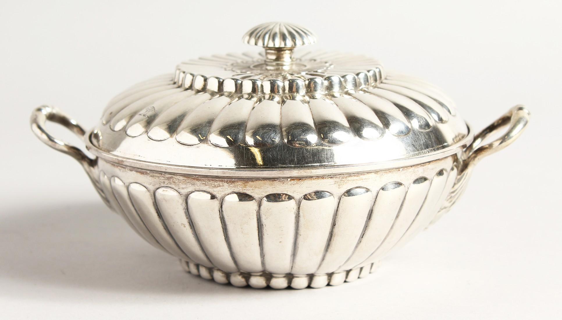 A GEORGE II SILVER CIRCULAR TWO HANDLED ECULLE and cover with fluted decorations. 5.5ins diameter
