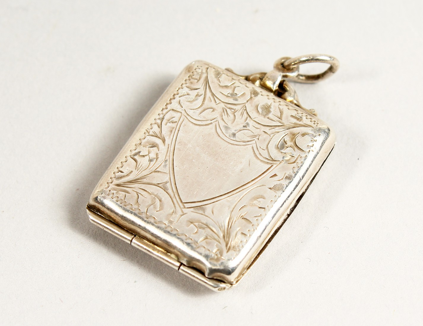AN ENGRAVED SILVER STAMP HOLDER.