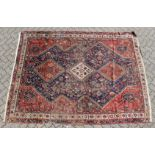 A PERSIAN CARPET with three large diamond design, in red and blue. 9ft long x 6ft 10ins wide.