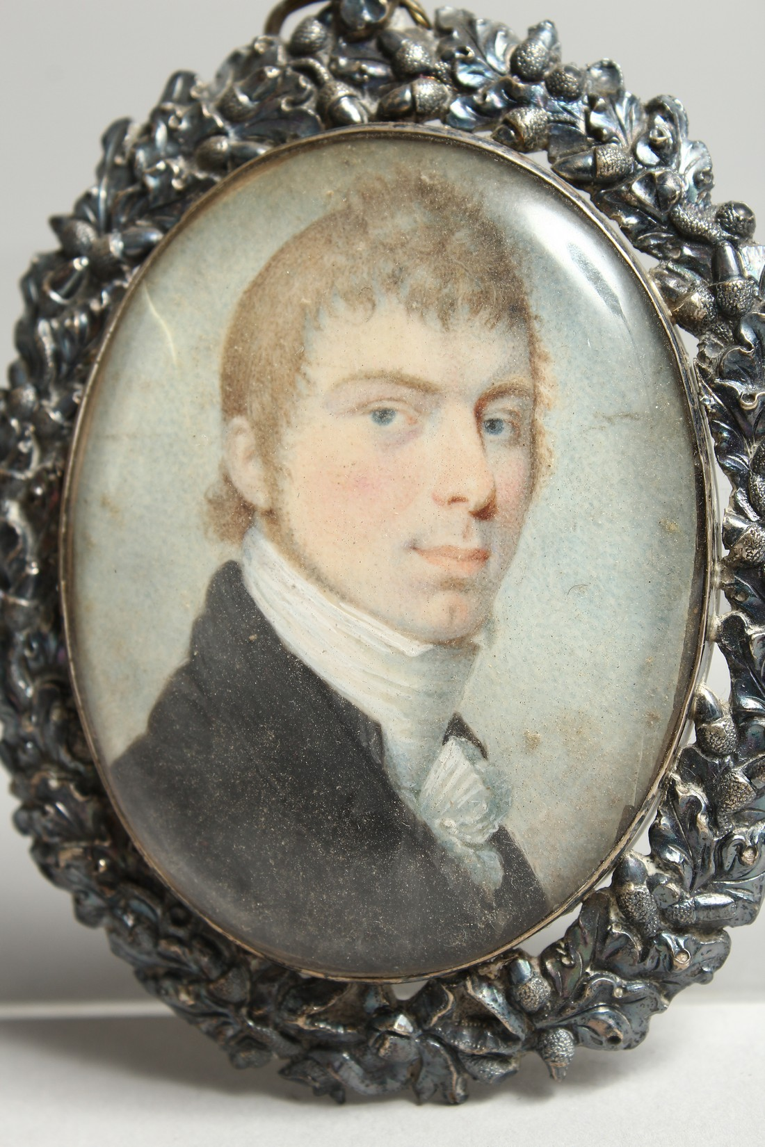 A GEORGIAN OVAL MINIATURE OF A YOUNG MAN, in a silver frame. 2.5ins x 2ins. - Image 2 of 3