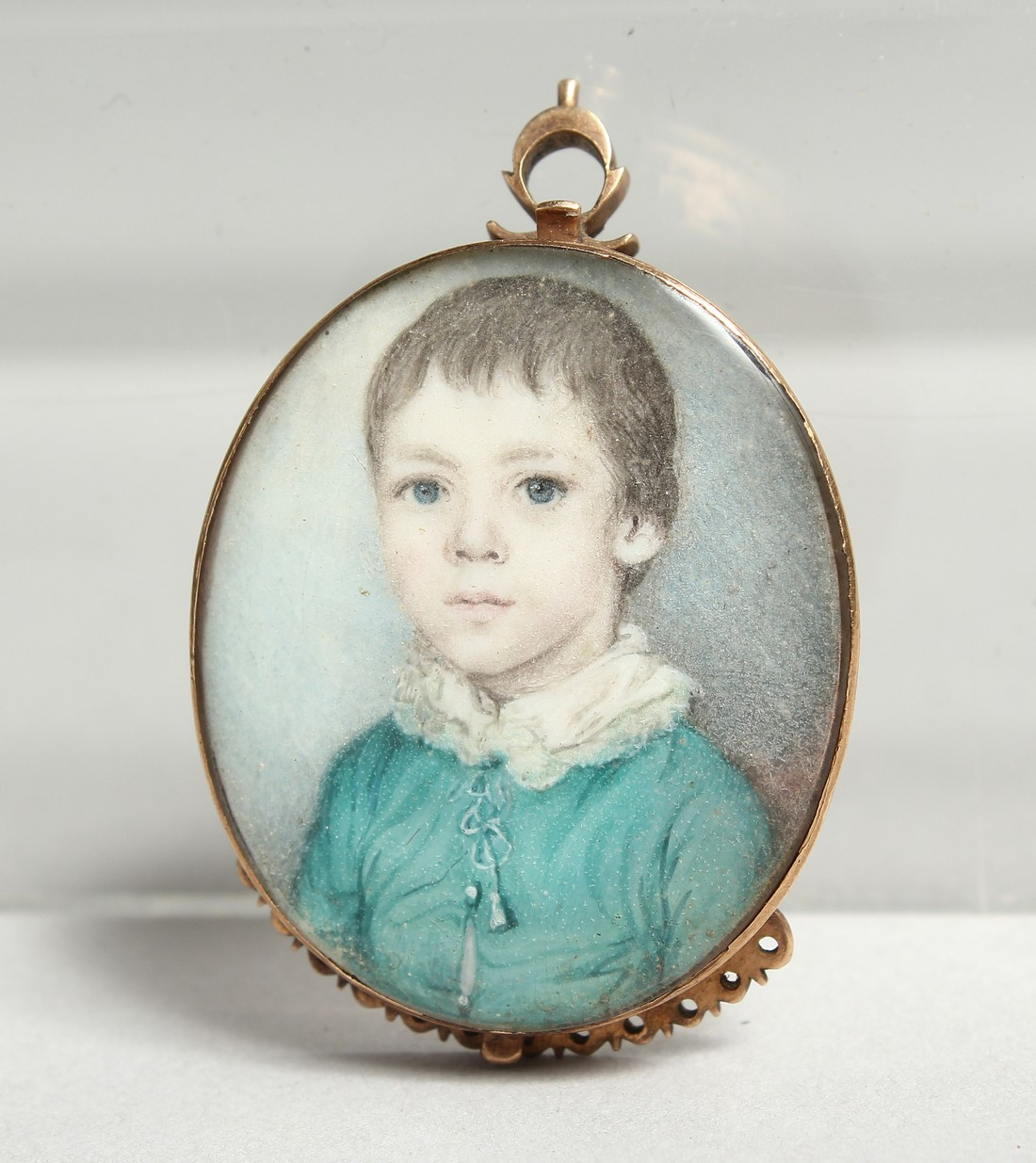 A GEORGIAN OVAL MINIATURE OF A YOUNG BOY, young boys in a gilt frame. 1.25ins x1ins