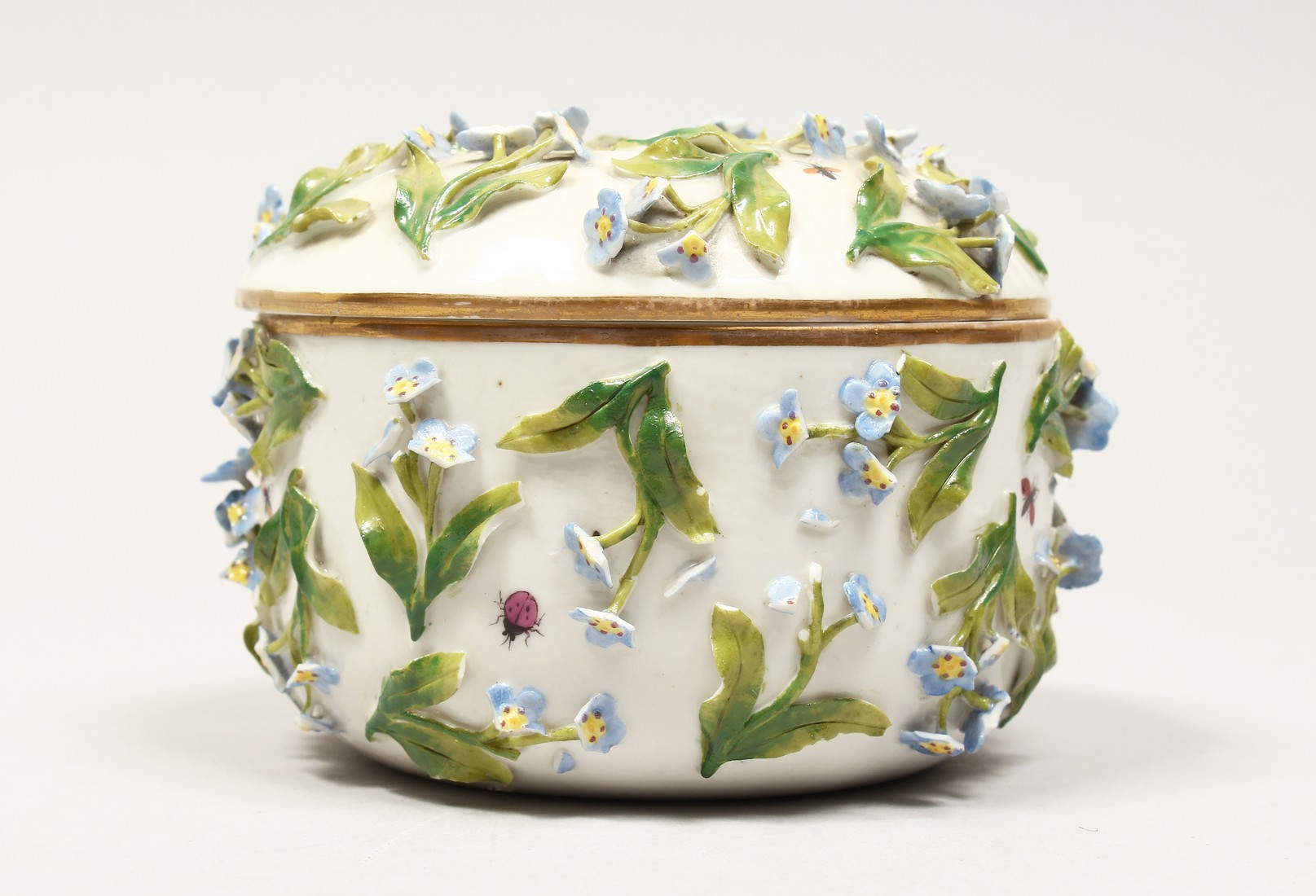 A DRESDON CIRCULAR BOWL AND COVER painted with moths and encrusted with flowers. 4.5ins diameter.