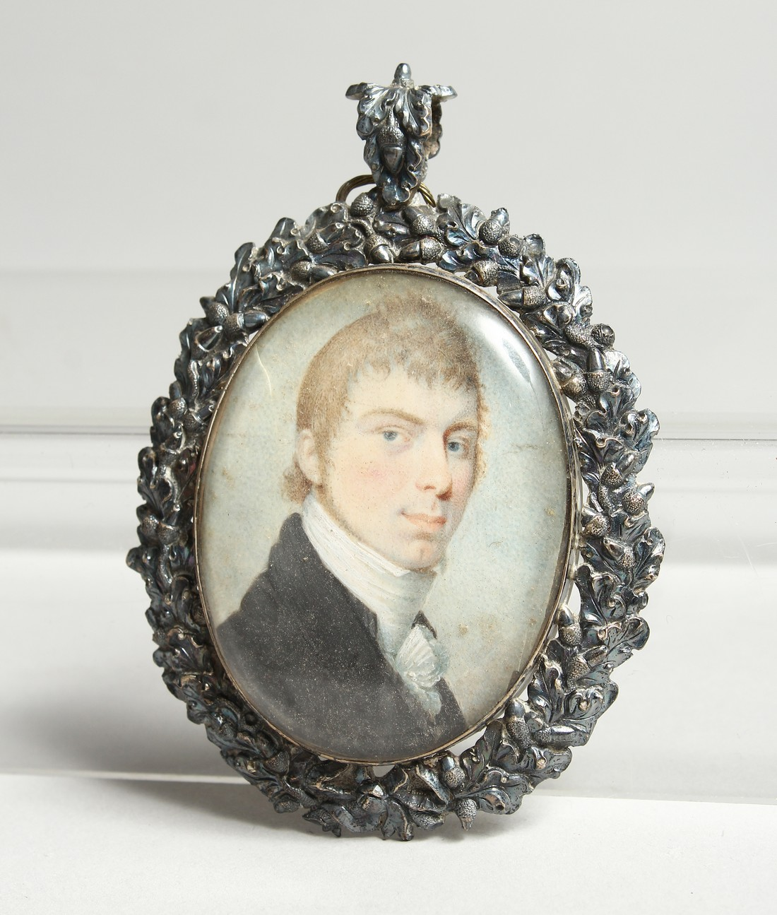 A GEORGIAN OVAL MINIATURE OF A YOUNG MAN, in a silver frame. 2.5ins x 2ins.