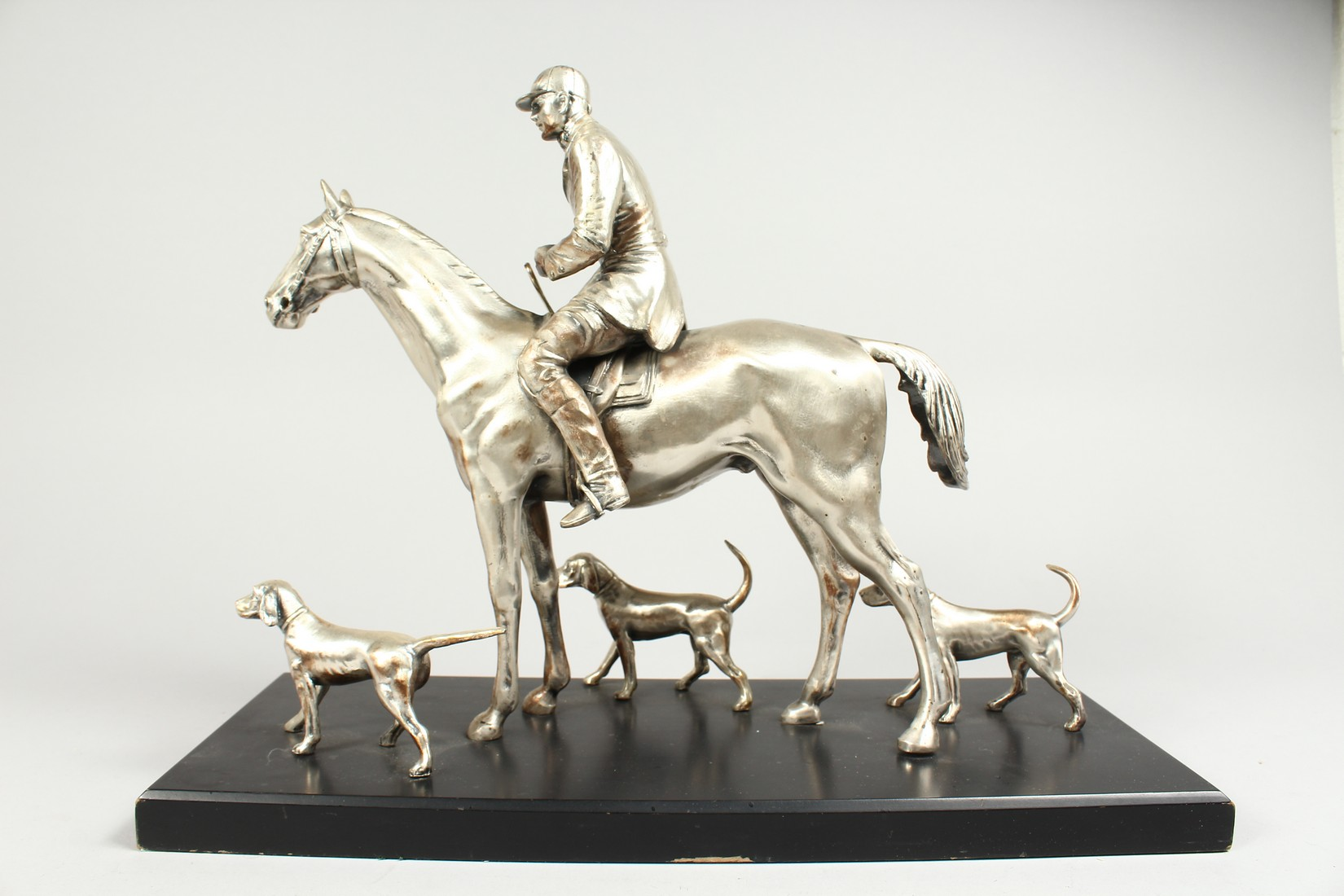 A SILVERED BRONZE GROUP HORSE AND RIDER, with their dogs, on a wooden base. 17ins long, 12ins high. - Image 2 of 10