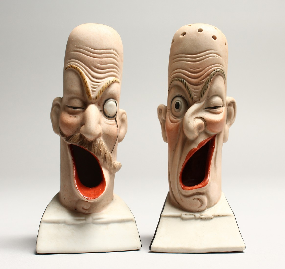 A PAIR OF POTTERY MEN'S HEADS ASHTRAYS. 5in high.