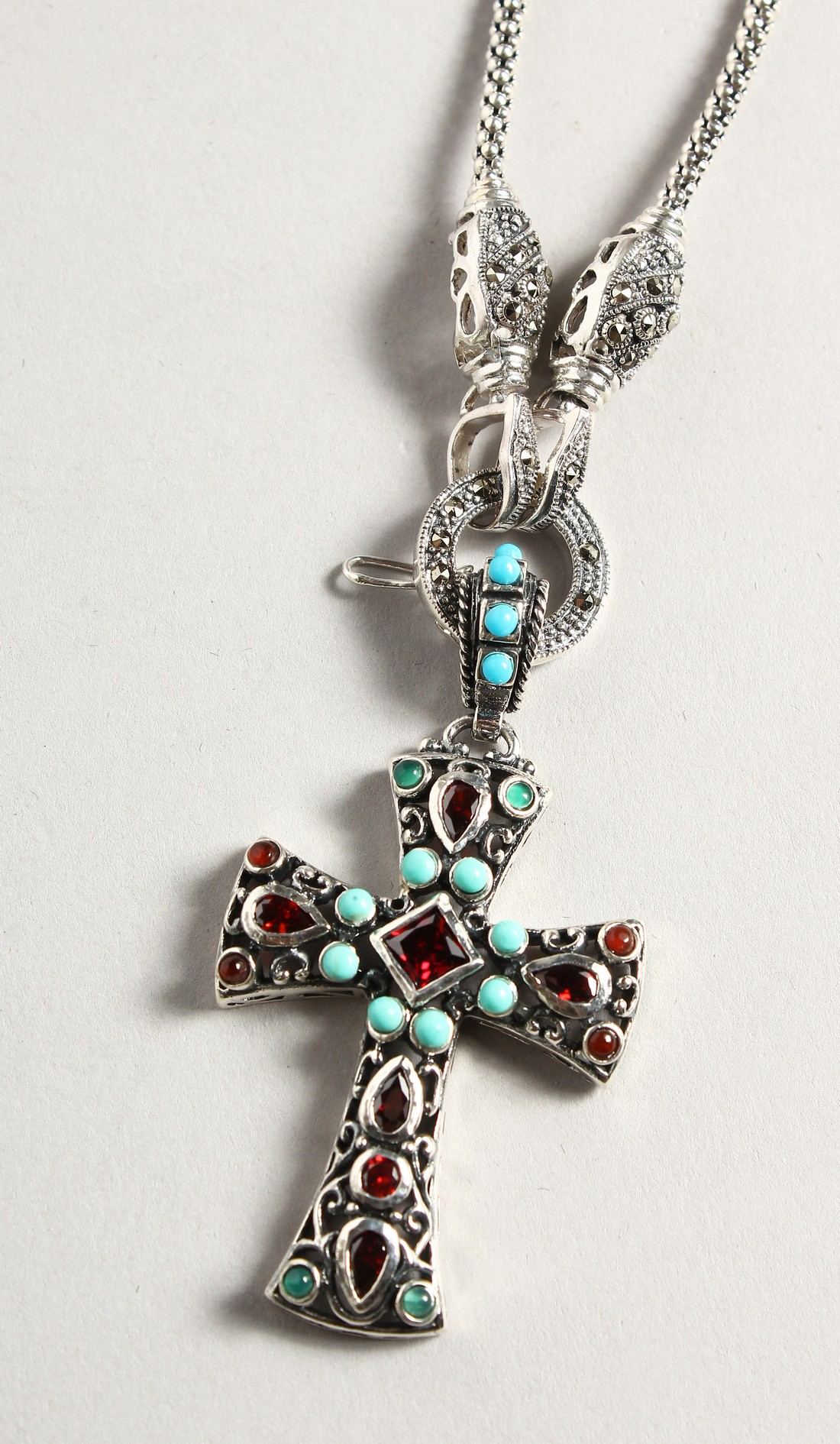 A SILVER TURQUOISE AND GARNET CROSS on a silver chain.