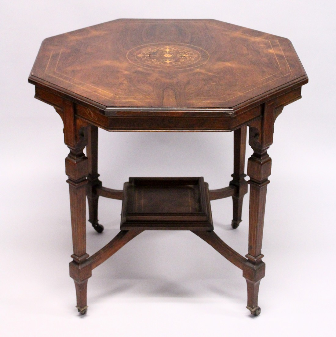 A GOOD VICTORIAN ROSEWOOD OCTAGONAL CENTRE TABLE with inlaid top, tapering legs with casters and