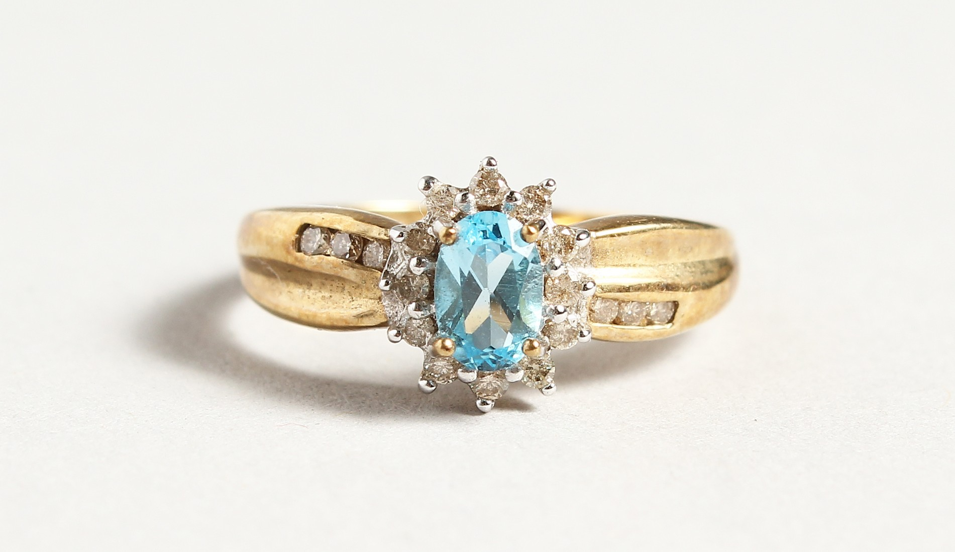 A 9CT GOLD BLUE TOPAZ AND DIAMOND CLUSTER RING