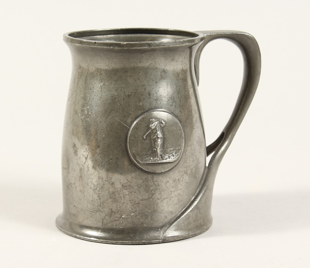 A TUDRIC ARCHIBALD KNOX PEWTER TANKARD with an oval of a golfer No. 066 4.25ins high.