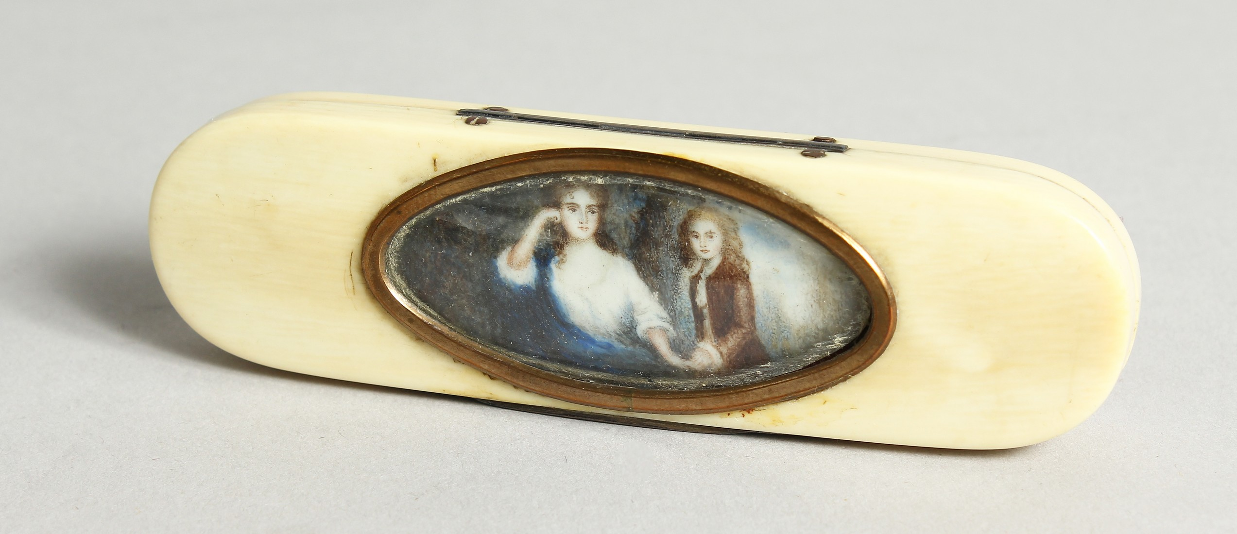 A GEORGIAN IVORY LONG PINBOX, the top with an oval, lady and young boy. 4ins long.