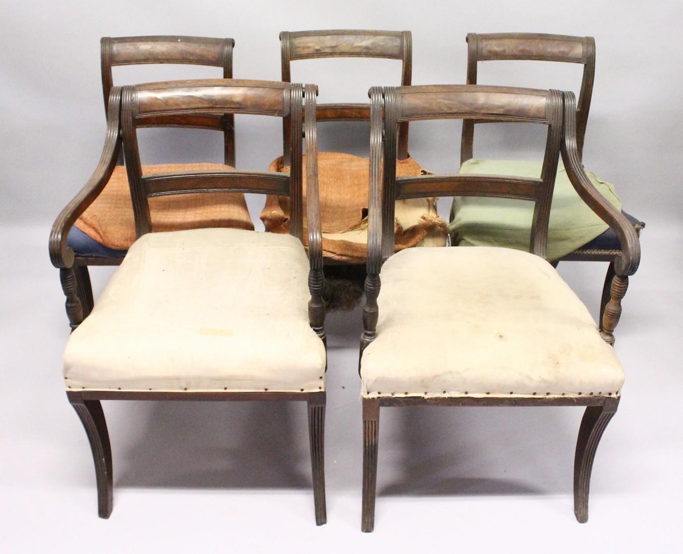 A PAIR OF MAHOGANY, SABRE LEG ARM CHAIRS and three matching single chairs.