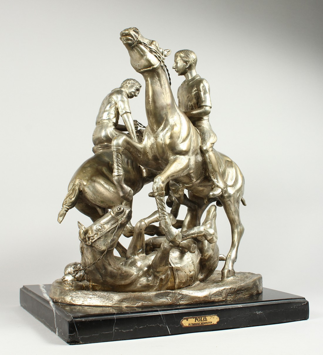 AFTER F. REMMINGTON A SILVER BRONZE GROUP OF TWO RIDERS ON HORSEBACK, a horn and rider on the floor.