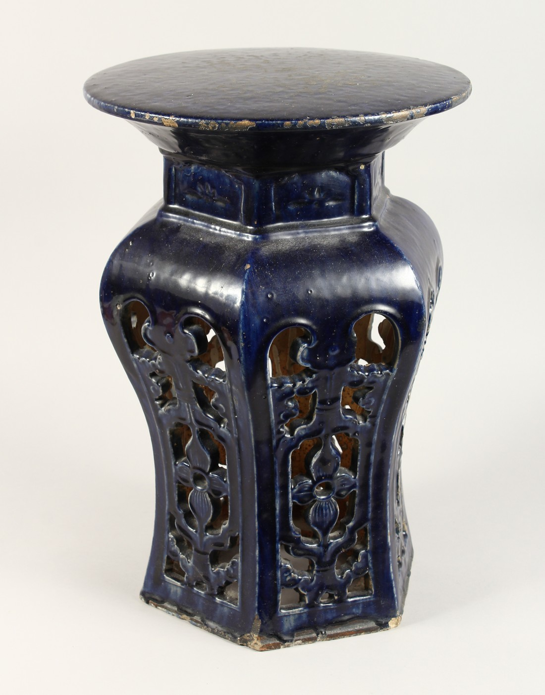A CHINESE POTTERY SEAT with circular top and pierced sides. 1ft 8ins high.