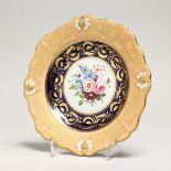 A GOOD COALPORT PLATE, rich gilt border, the centre painted with flowers 8ins diameter.