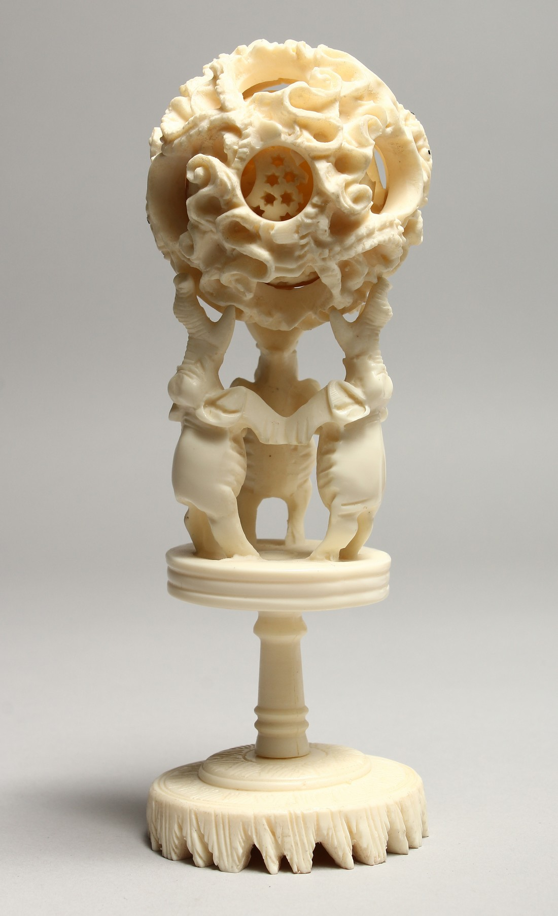 A FAUX IVORY PUZZLE BALL on a stand. 7ins high