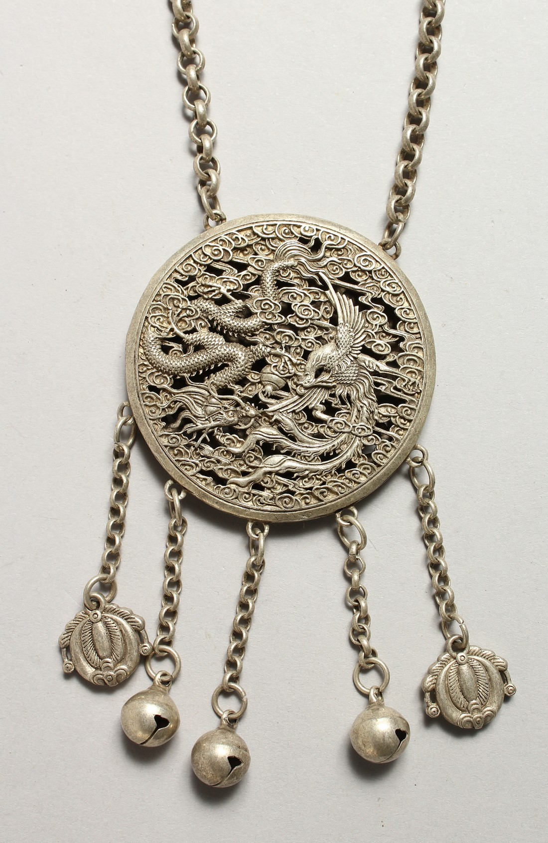 A CHINESE SILVER YIN-YANG PENDANT on a chain with dragon and phoenix.