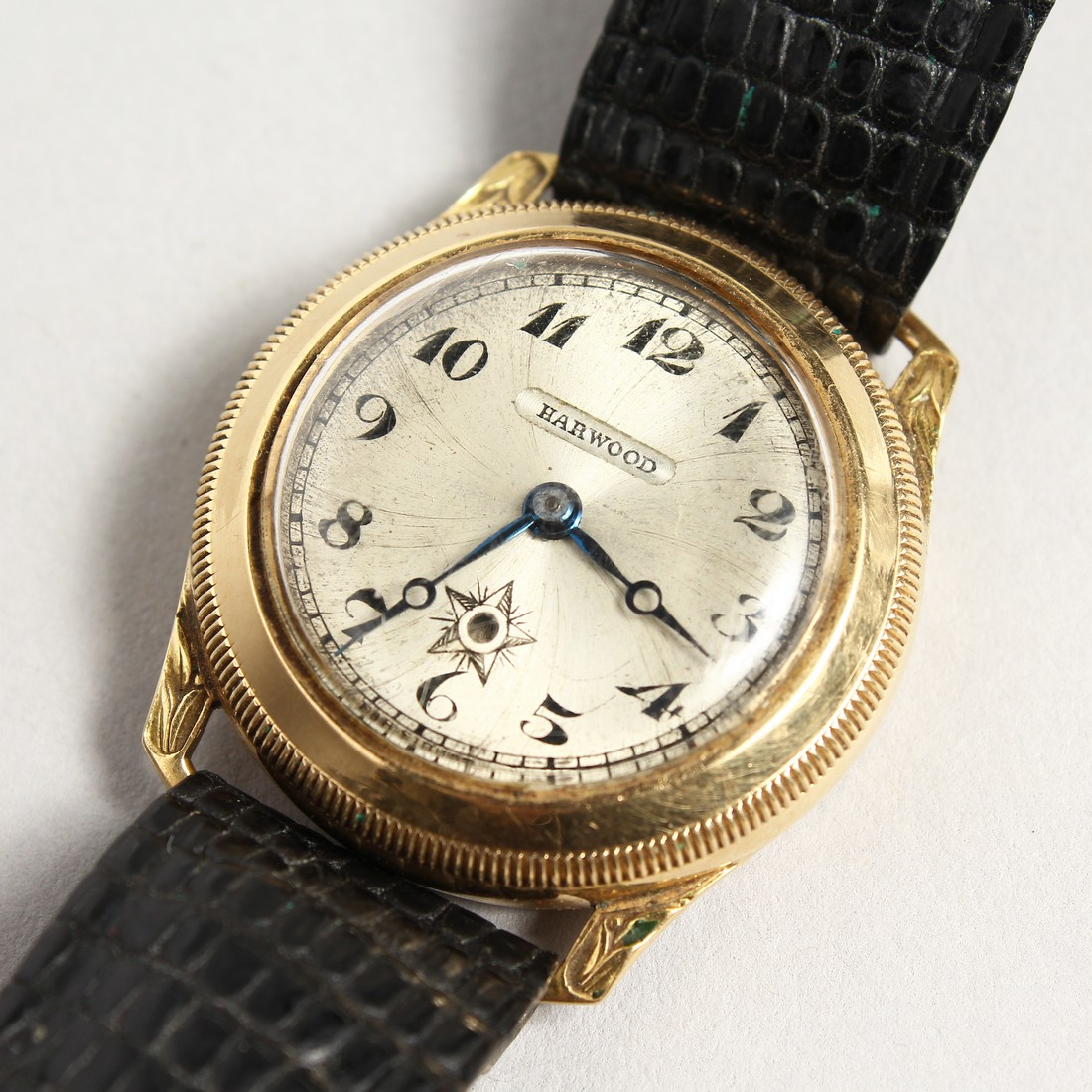 A HARWOOD GOLD WRISTWATCH with leather strap.