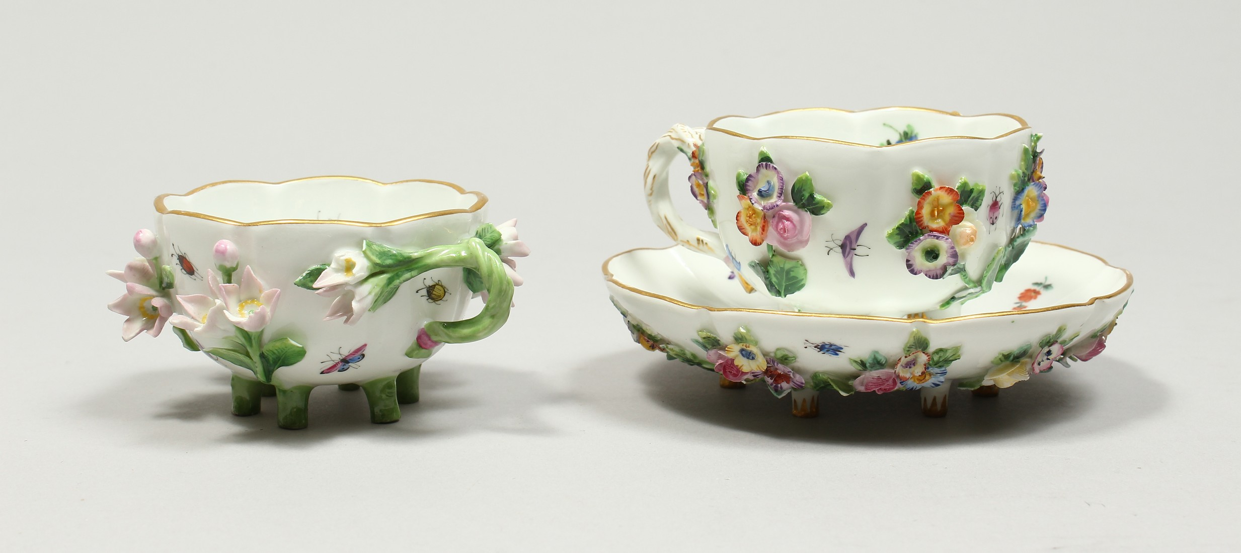 TWO MEISSEN PORCELAIN CUPS AND SAUCERS AND A SAUCER, encrusted with flowers and painted with