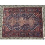 AN OLD PERSIAN RUG with three medallions (worn). 5ft 5ins long x 4ft 6 ins wide.
