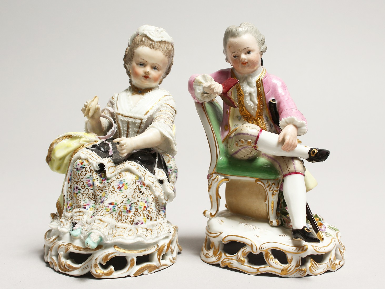 A GOOD PAIR OF MEISSEN PORCELAIN FIGURES, a young man reading a book, a girl sewing. Cross swords