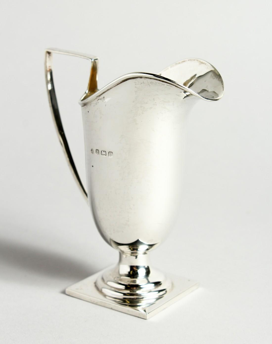 A HELMET-SHAPED SILVER CREAM JUG on a square base. Birmingham 1908. 12cm tall - 78g