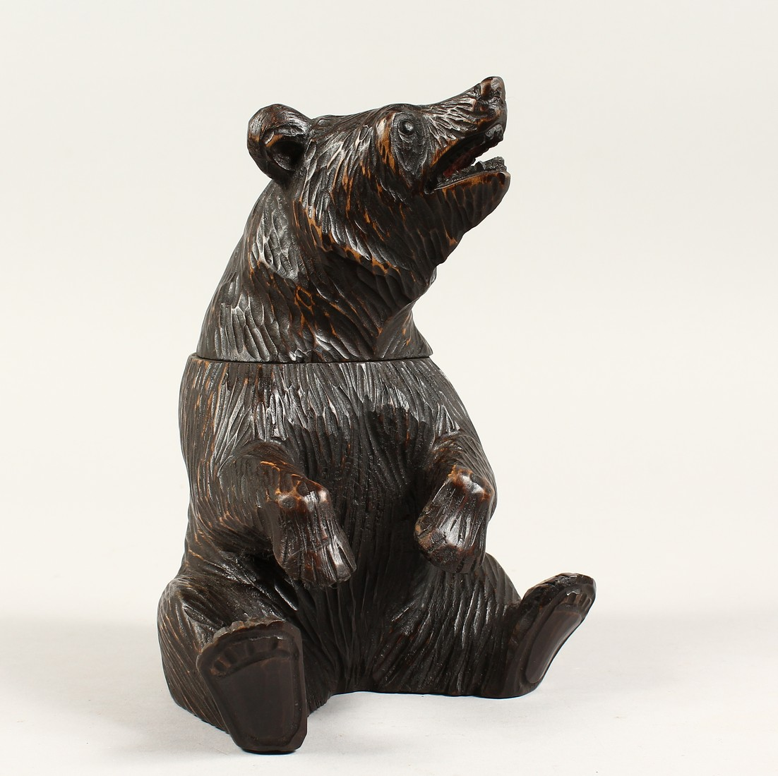 A BLACK FOREST CARVED WOOD BEAR CADDY. 8ins high.