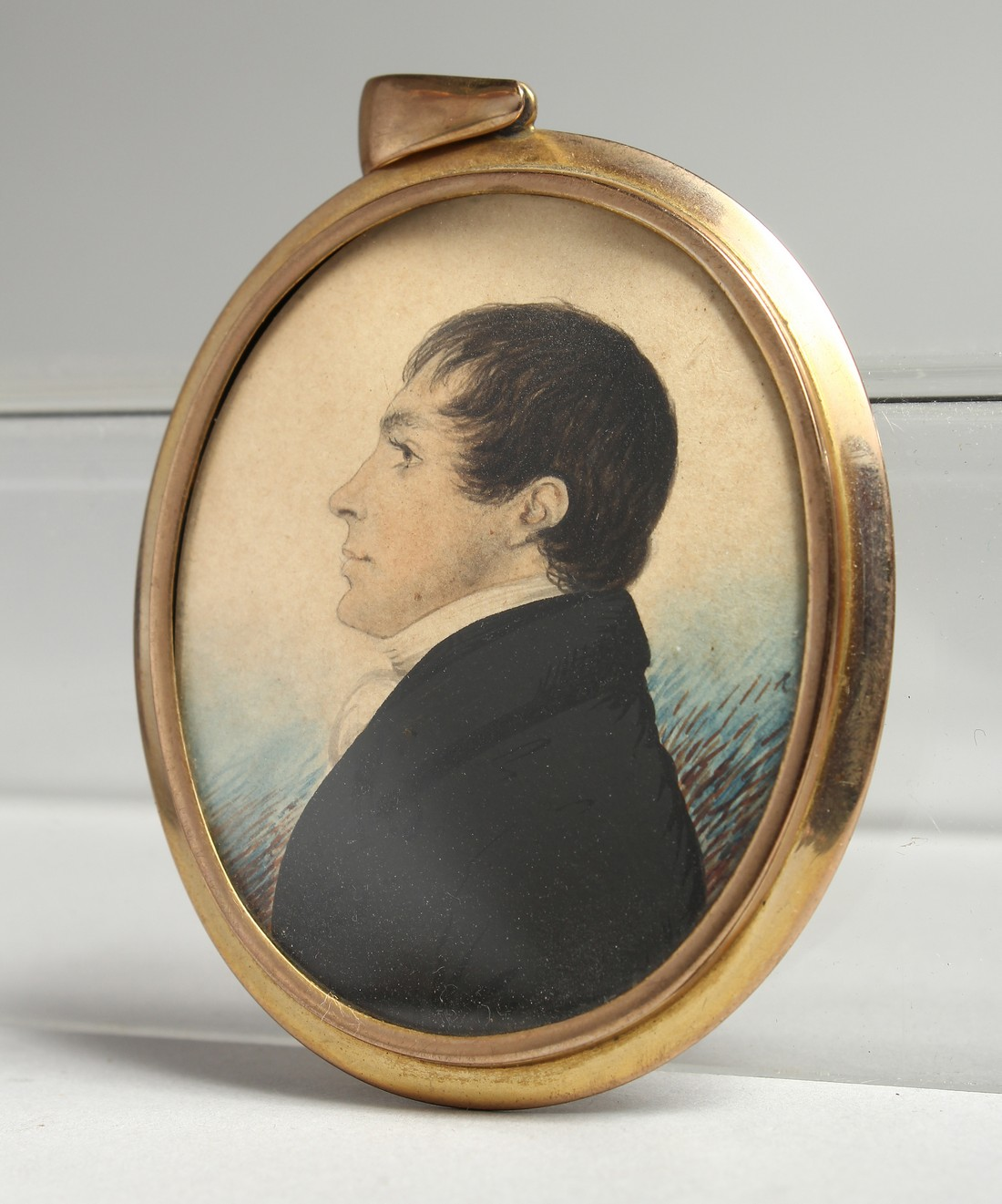 AN EARLY VICTORIAN OVAL MINIATURE OF A GENTLEMAN in a gilt frame. 2.25ins x 1.75ins