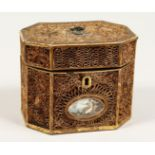 A GEORGE III ROLLED PAPER OCTAGONAL TEA CADDY inlaid with an oval. 5.5ins long.