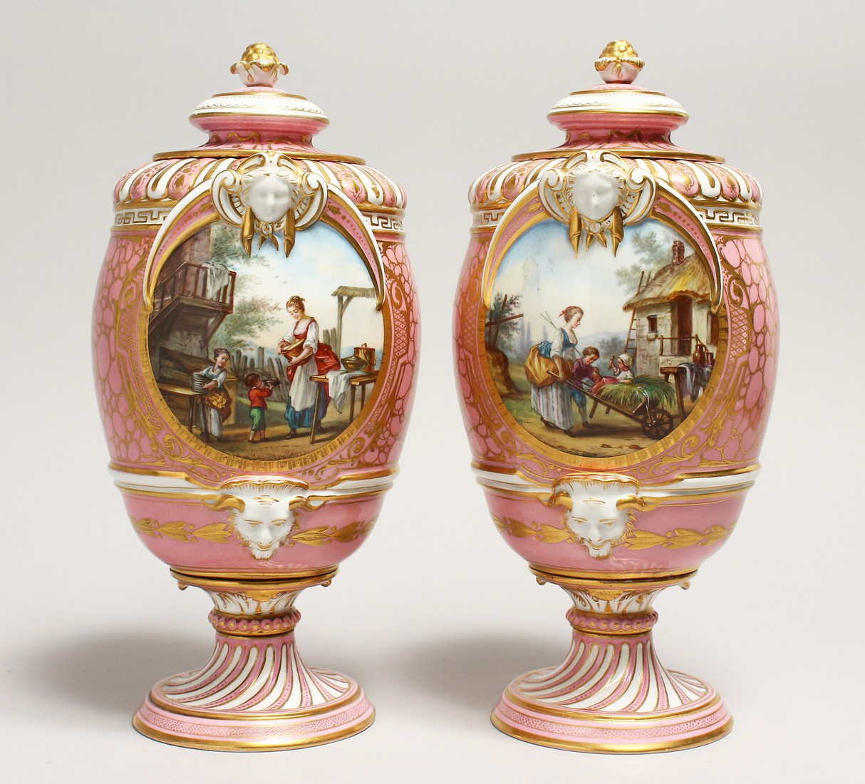 A VERY GOOD PAIR OF SEVRES PINK GROUND VASES AND COVERS each painted with reverse panels of figures,