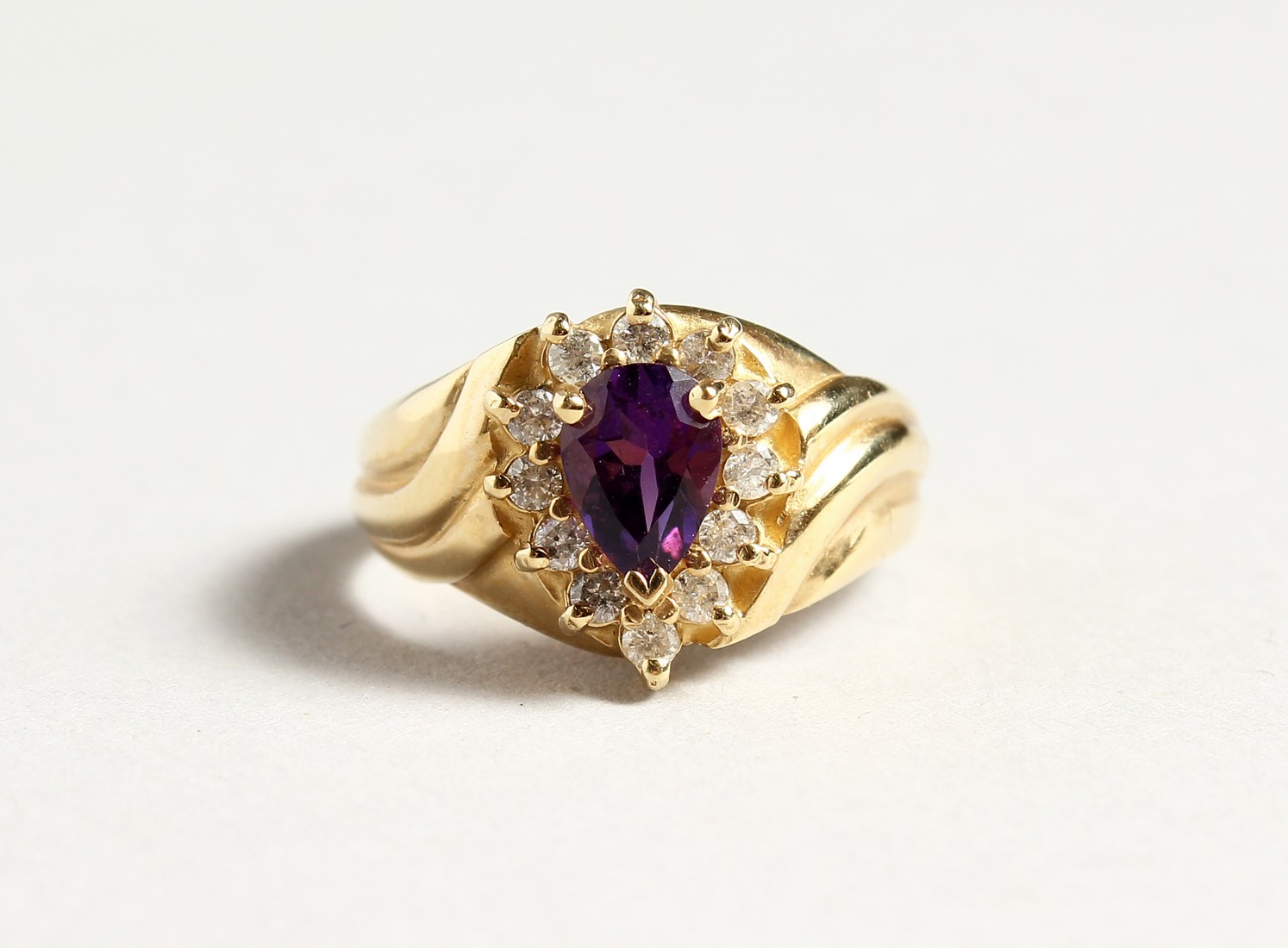 A 14CT GOLD, AMETHYST AND DIAMOND TEAR DROP RING