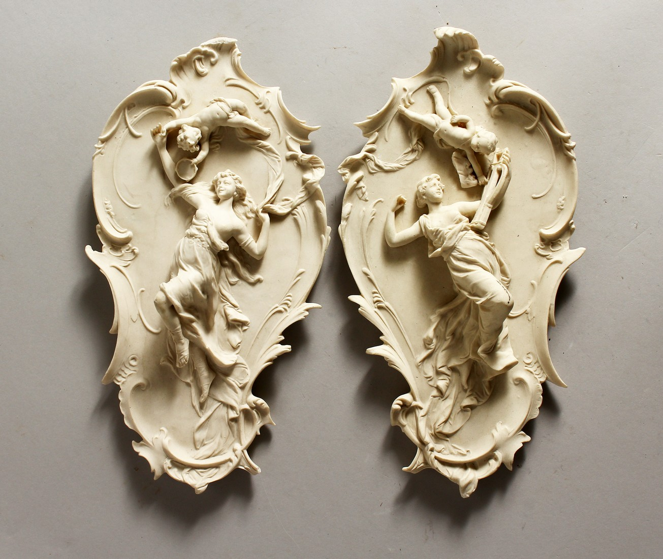A PAIR OF NOUVEAU STYLE PLAQUES with classical figures 13ins long