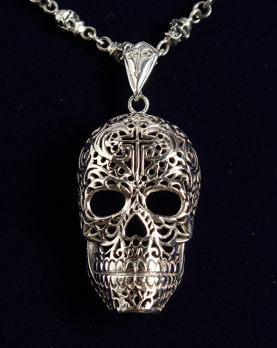 A SILVER SKULL ON A CHAIN.