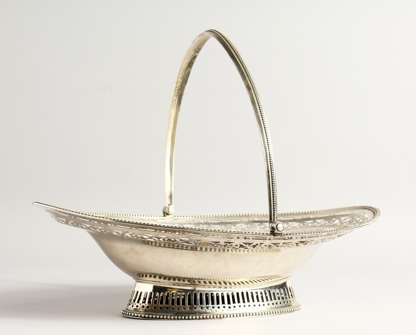 A FINE GEORGE III SILVER CAKE BASKET by HESTER BATEMAN with bead edges and swing handles. London