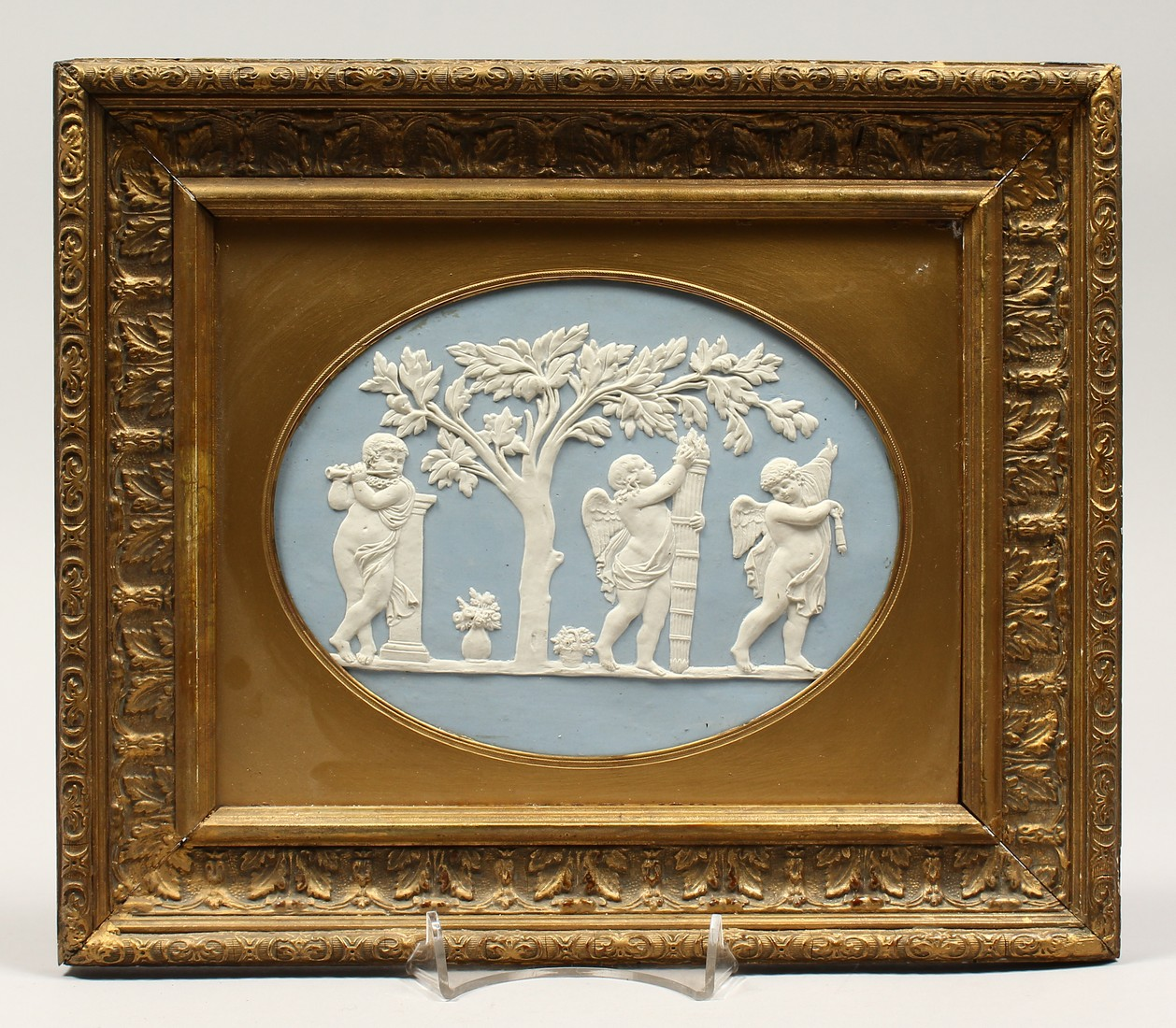 A WEDGWOOD BLUE AND WHITE GILT FRAMED PORCELAIN PLAQUE with cupids 6ins and 8ins.