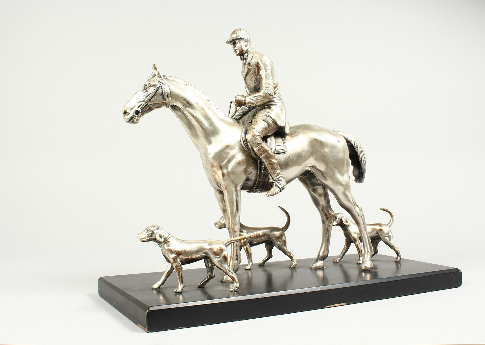 A SILVERED BRONZE GROUP HORSE AND RIDER, with their dogs, on a wooden base. 17ins long, 12ins high.