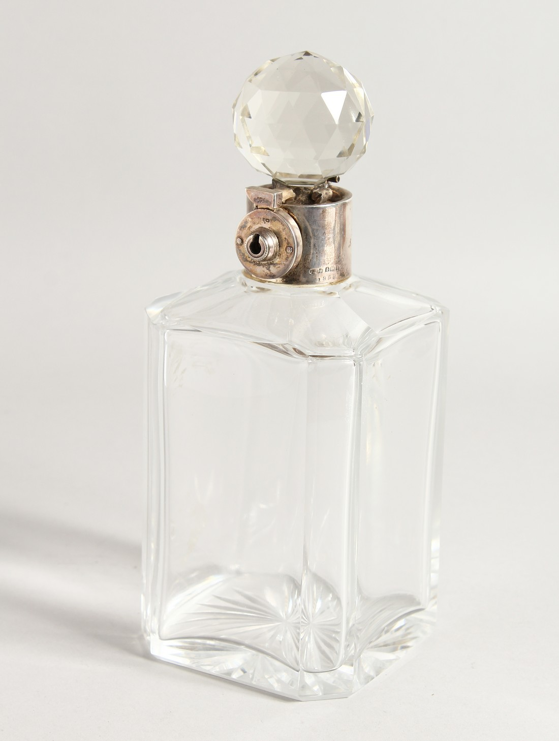 A HEAVY SQUARE GLASS WHISKY DECANTER AND STOPPER with silver band.