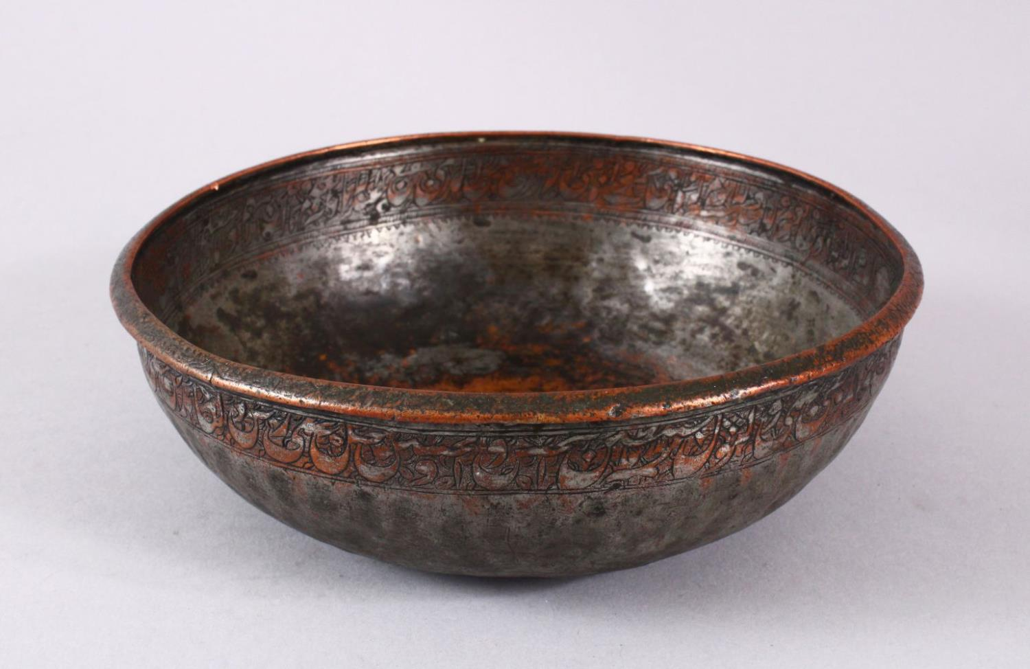 A UNUSUAL ISLAMIC TINNED HAMMERED COPPER CALLIGRAPHIC BOWL, decorated with interior & exterior bands