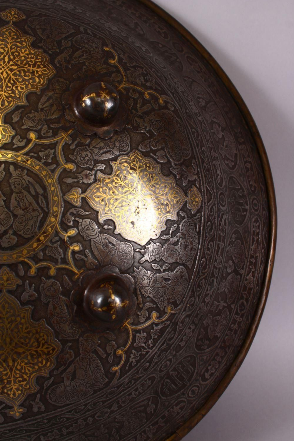A LARGE 19TH CENTURY PERSIAN GILT DECORATED STEEL SHIELD, with carved decoration of figures, bands - Image 5 of 12