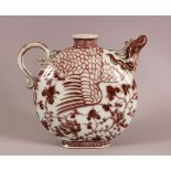A CHINESE MING STYLE COPPER RED PHOENIX PORCELAIN POURING VESSE, with a moulded phoenix head handle,