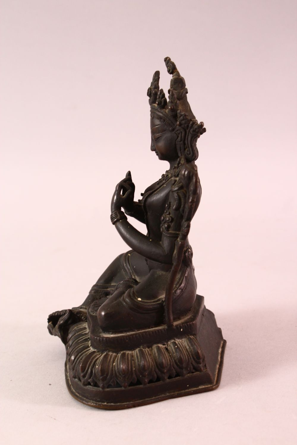 A 19TH CENTURY INDIAN BRONZE FIGURE OF SHIVA / DEITY, in a seated pose with hands together, upon - Image 4 of 5