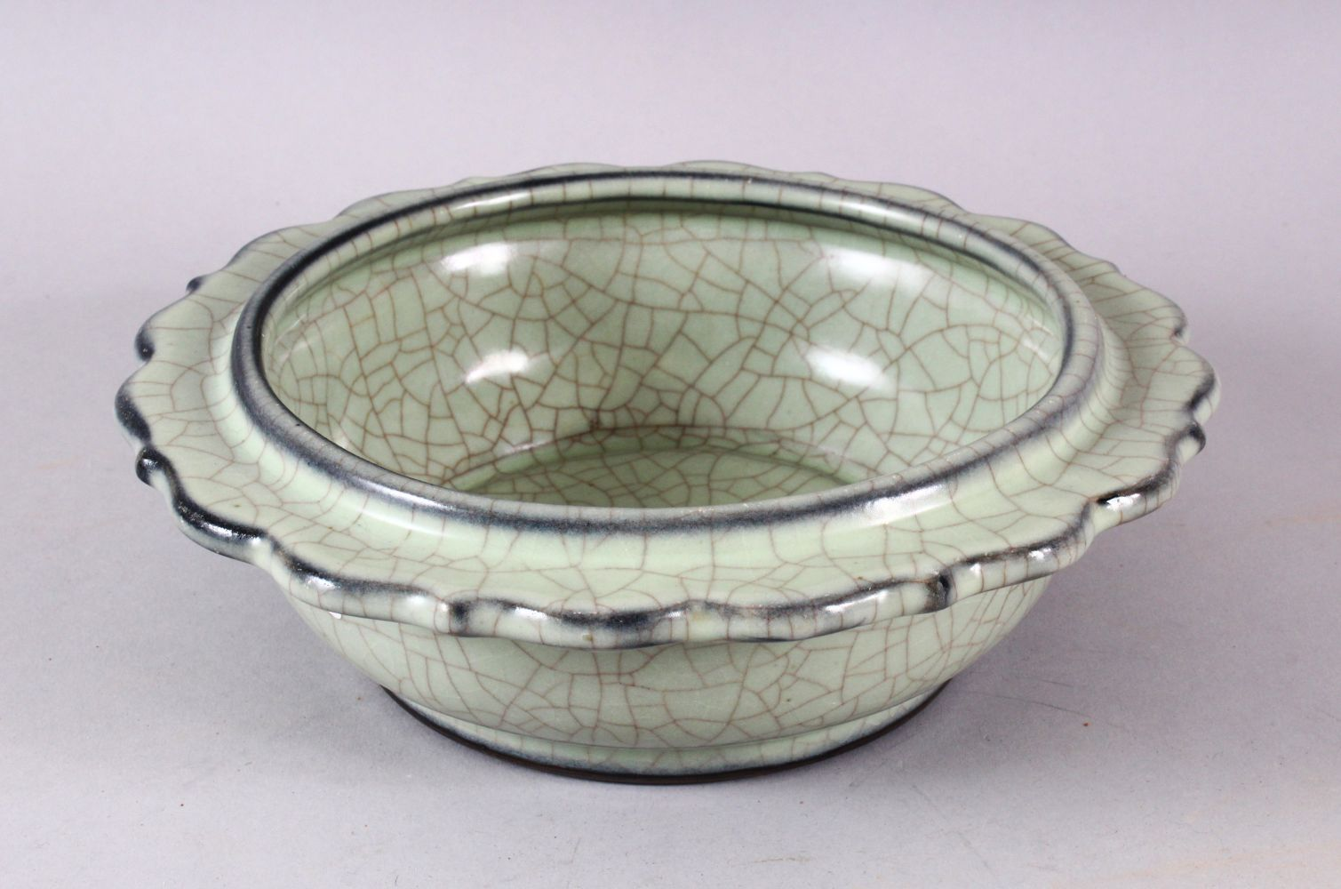 A CHINESE BARBED RIM GUAN GLAZED POTTERY DISH, the flared rim with ironwire style body decoration,