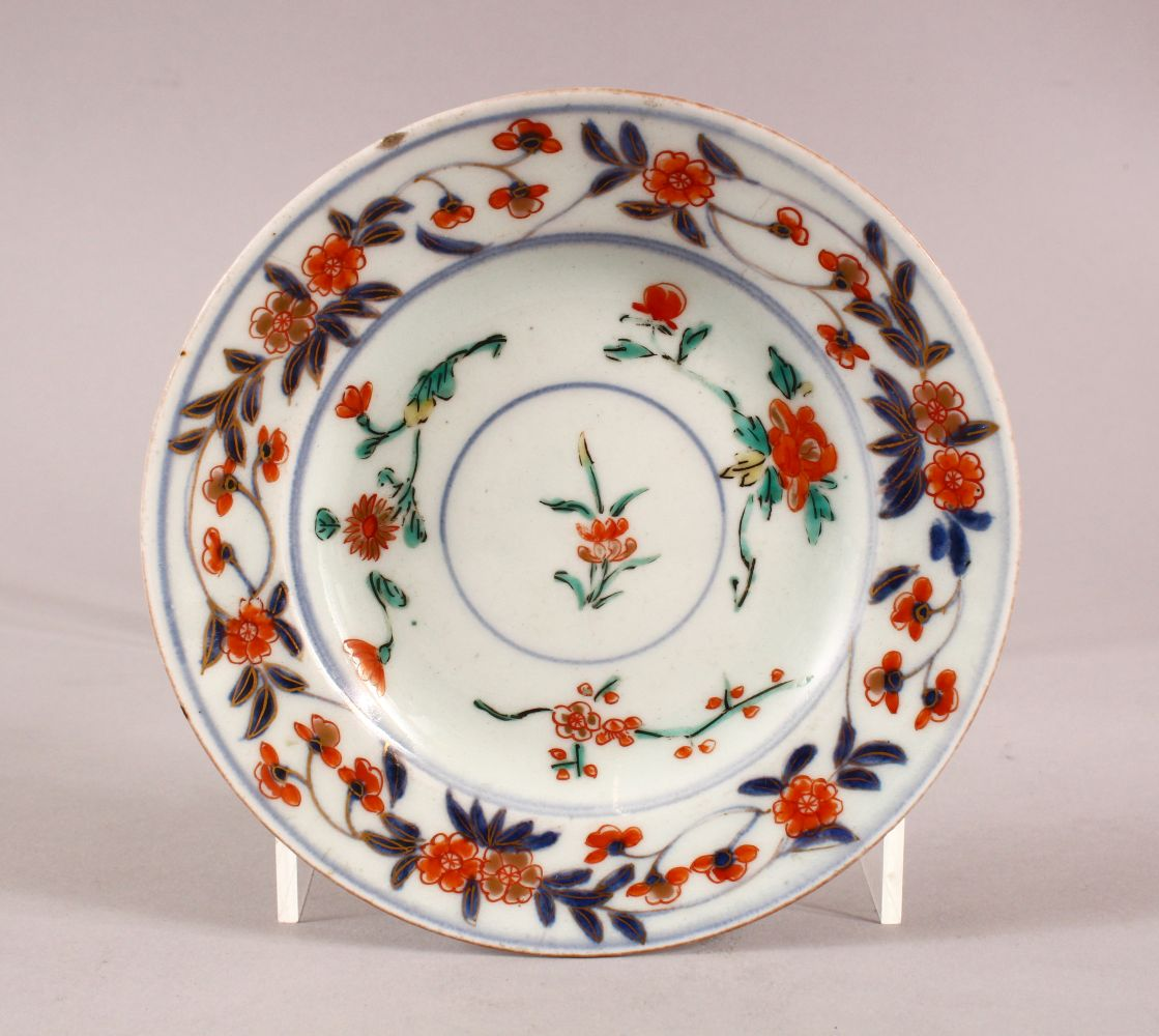 A SMALL JAPANESE IMARI CIRCULAR STAND, painted with a band of flowers on three scrolling feet, 13.