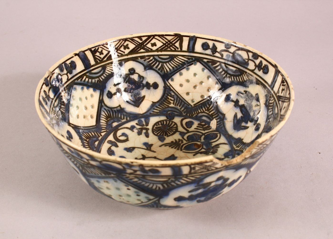 A 19TH CENTURY OR EARLIER TURKISH POTTERY BOWL, with floral motif decorations, (af) 18.5cm